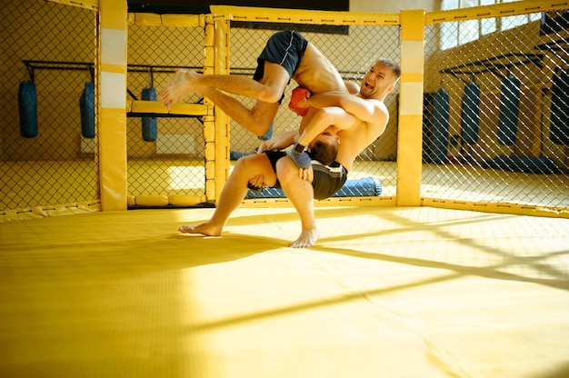 Male mma fighter performs a throw through himself in a cage in gym.