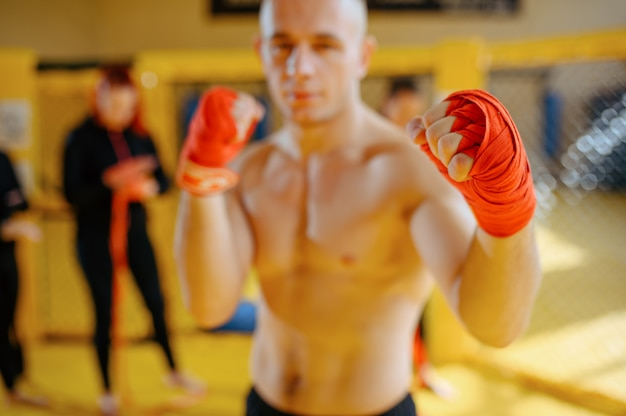 Male mma fighter with red bandages on his hands in gym.