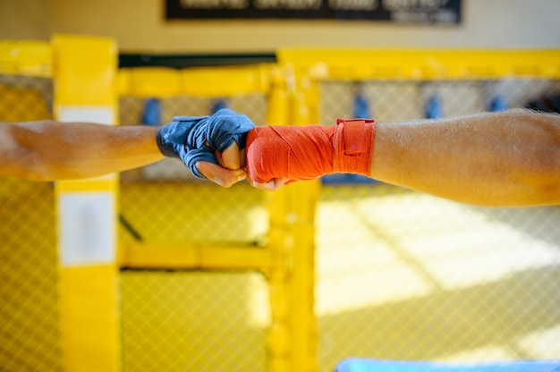 Male mma fighters hands with red and blue bandages in  gym interior