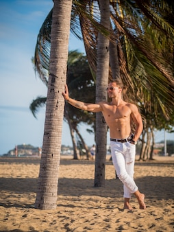 Male model on the beach. palm trees on sunset time