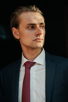 Male model in black suit and red tie poses for men's clothing advertising. shooting for men's clothing store
