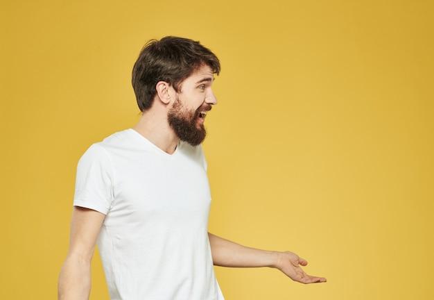 黄色の背景のトリミングされたビューで彼の手で身振りで示す男性モデル
