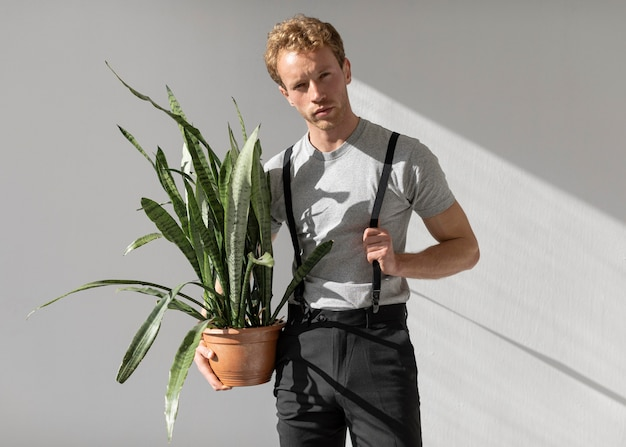 Male model holding a plant front view