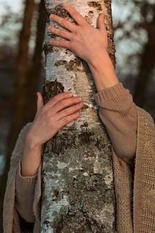 木を抱き締める男性モデル
