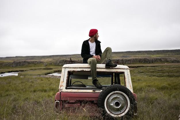 ジャンクヤードの車の上にクールな服装の男性モデル