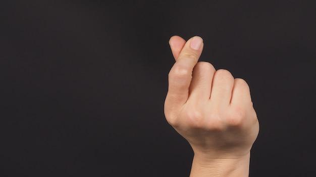 Мужская модель делает знак рукой мини-сердце на черном фоне.