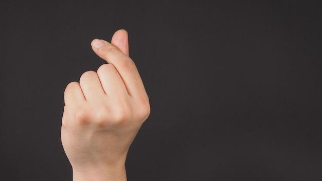 Мужская модель делает знак рукой мини-сердце левой рукой на черном фоне.