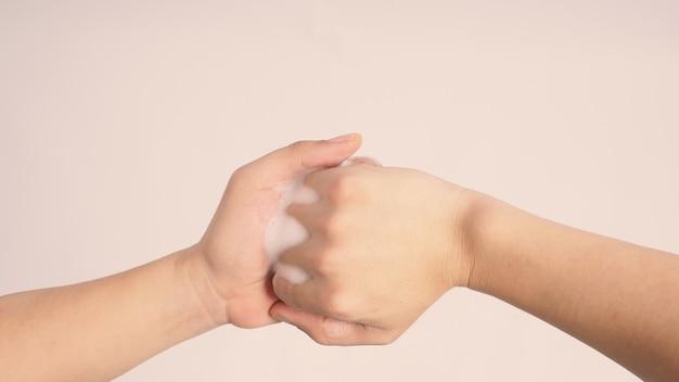 남성 모델은 손가락을 맞물리고 흰색 배경에 거품이 나는 손 비누로 중간 관절을 문지릅니다.