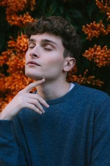 Male model posing beside flowers