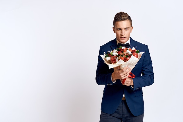 Male model posing in a classic business suit in the studio on a wall with a bouquet of flowers