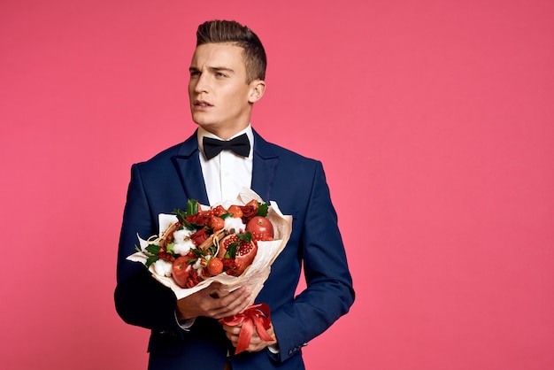 Male model posing in a classic business suit with a bouquet of flowers