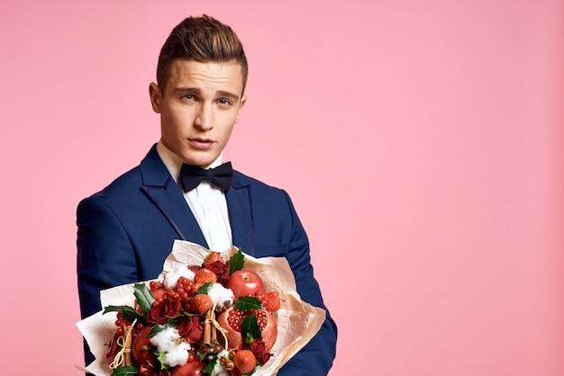 花の花束を保持している古典的なビジネススーツでポーズをとる男性モデル