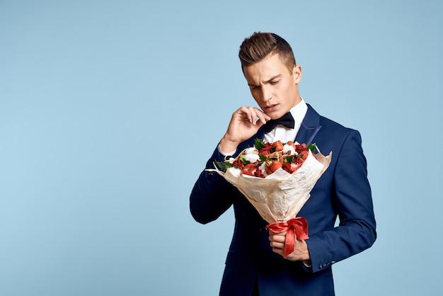 花の花束が付いている壁の古典的なビジネススーツでポーズをとる男性モデル