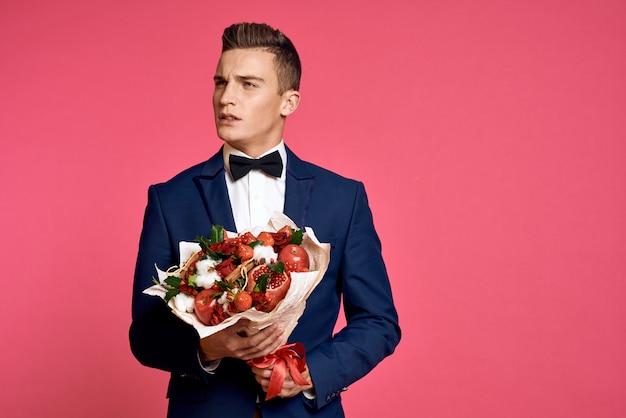 花の花束を持つ古典的なビジネススーツでポーズをとる男性モデル
