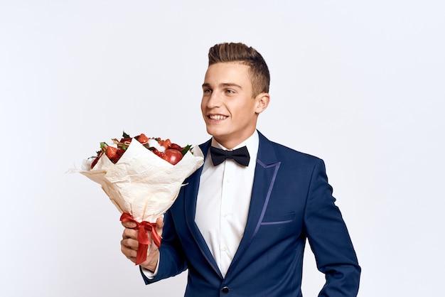 Мужская модель позирует в классическом деловом костюме с букетом цветов