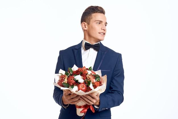 花の花束とクラシックなビジネススーツでポーズをとる男性モデル