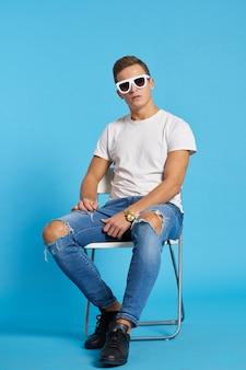 Мужская модель позирует в джинсах и белой футболке на голубом