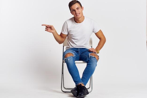 ジーンズと明るい壁に白いtシャツでポーズをとる男性モデル