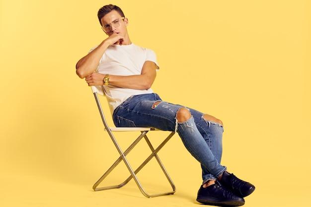 ジーンズと明るい黄色の背景に白いtシャツでポーズをとる男性モデル
