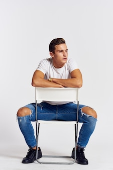 Male model posing in jeans and a white t-shirt on a light background