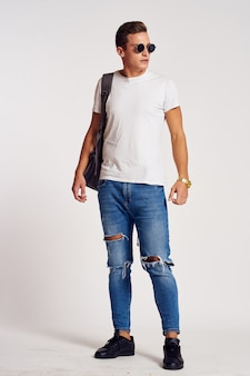 Male model posing in jeans and a white t-shirt on a light wall