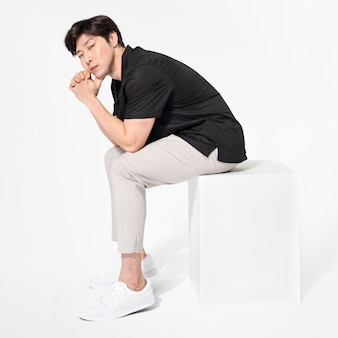 Male model posing and sitting on a chair in minimal outfit full body