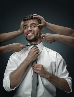 Un modello maschile circondato da mani come i suoi pensieri su un muro scuro. un giovane dubita, è sotto la pressione delle situazioni della vita. concetto di problemi mentali, problemi di lavoro, indecisione.