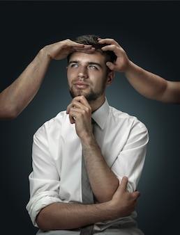 暗い背景に彼自身の考えのように手に囲まれた男性モデル。