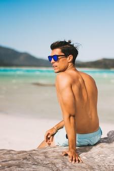 Мужские модели носить солнцезащитные очки и фитнес тела на пляже позирует