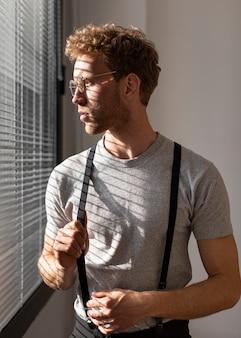 Мужская модель с вьющимися волосами, глядя в окно, вид спереди