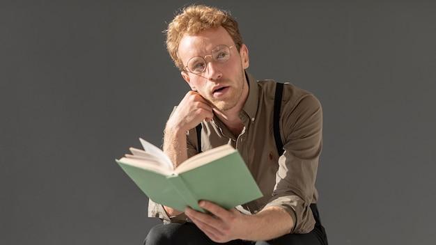 巻き毛の読書を持つ男性モデル