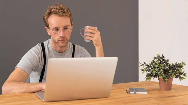 Male model with curly hair working on his laptop