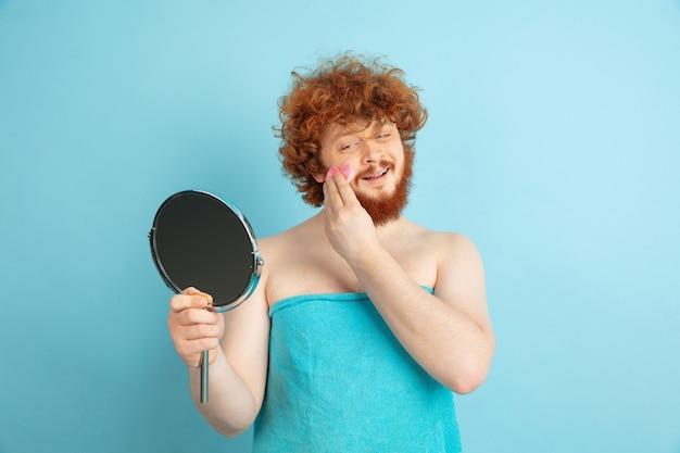 Modello maschile con capelli rossi naturali che applicano crema idratante, oli sulla pelle del viso