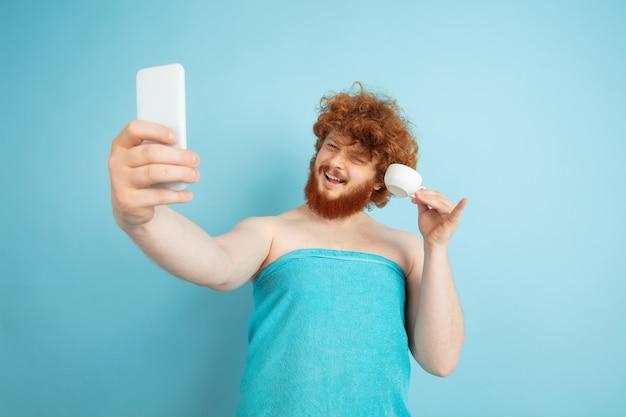 Modello maschio con capelli rossi naturali che prendono selfie in asciugamano