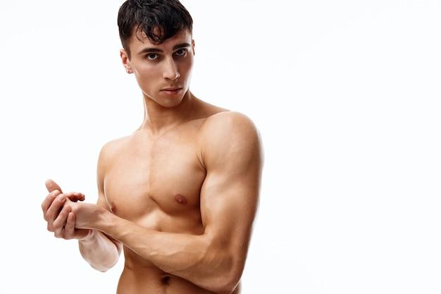 腕のポンプアップされた筋肉を持つ男性モデルは、白い背景の横に見えます