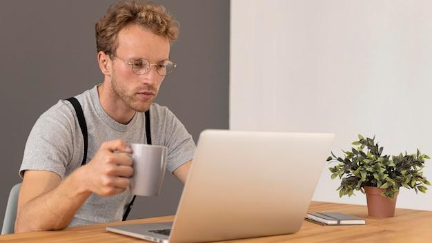 Мужская модель работает на своем ноутбуке и пьет кофе