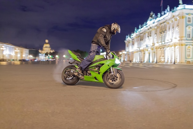 Male motorcyclist drifted night on your his sport motorcycle.