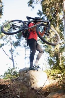 森で自転車を運ぶ男性のマウンテンバイク