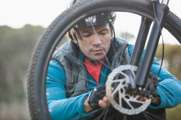 Мужской горный байкер осматривает переднее колесо своего велосипеда