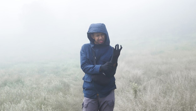 Male mountaineer putting on his gloves