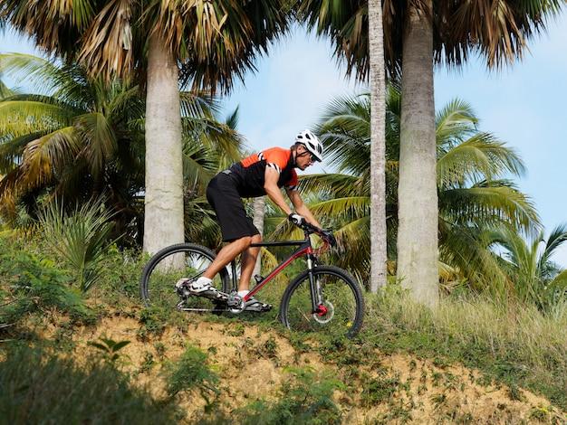Мужской mountian велосипедист на тропической тропе, взгляде со стороны. на открытом воздухе.