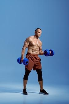 Male muscular athlete holds dumbbells in studio