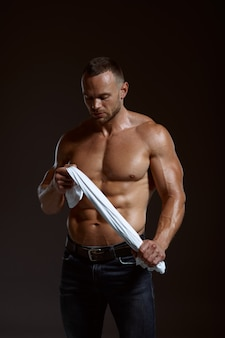 Male muscular athlete holds his shirt in hands in studio, dark background. one man with athletic build, shirtless sportsman in jeans pants, active healthy lifestyle