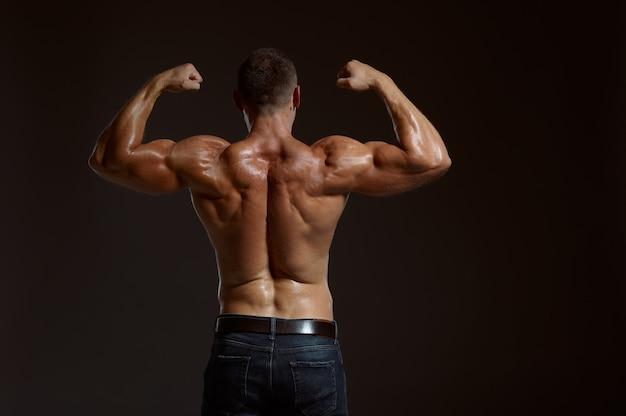 Мужской мускулистый спортсмен позирует в студии, вид сзади