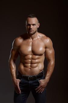 男性の筋肉アスリートは、スタジオ、暗い背景でポーズします。アスリートビルド、ジーンズパンツの上半身裸のスポーツマン、アクティブな健康的なライフスタイルを持つ一人の男