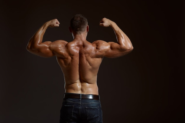 Male muscular athlete poses in studio, back view
