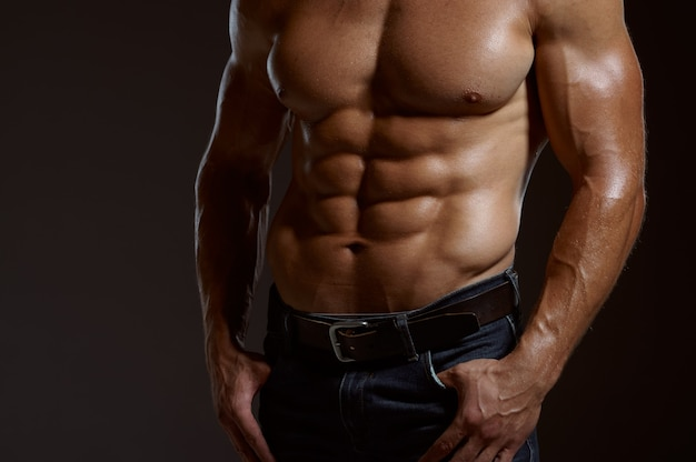 Male muscular athlete poses in studio