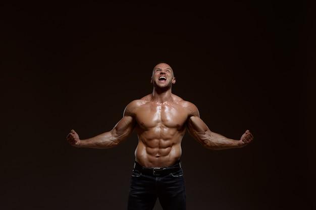 Мужской мускулистый спортсмен показывает свою силу в студии
