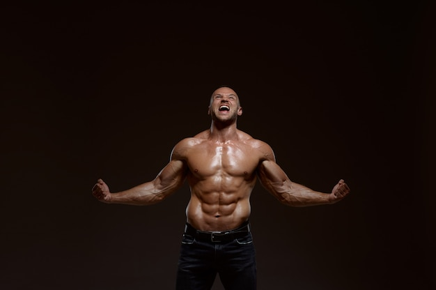 Male muscular athlete shows his power in studio