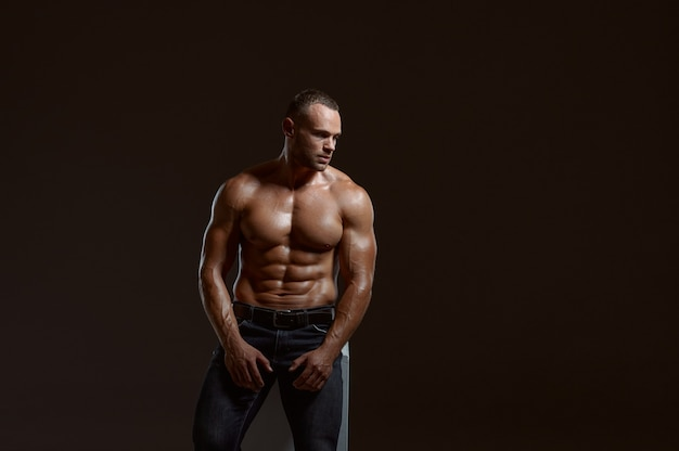 Male muscular athlete sitting on cube in studio
